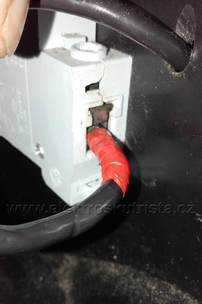 Detail vyhřáté svorky jističe elektroskútru s přívodním kabelem.